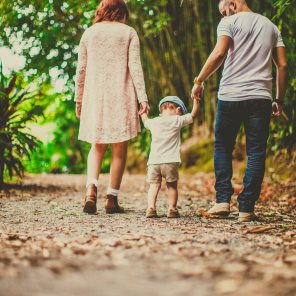 low-angle-shot-of-a-child-held-by-woman-and-man-on-on-each-3038455